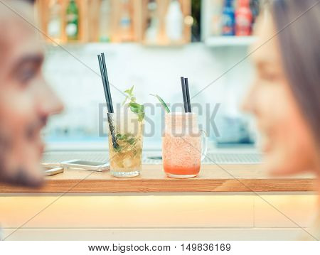 Young couple enjoying aperitif fashion cocktails in bar restaurant - Romantic cheerful lovers toasting drinks and looking each others - Love and relation concept - Vintage retro editing