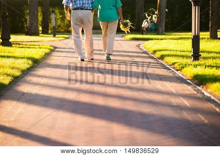 Legs of walking couple. Lady holding bouquet. Road of our life. Step by step.