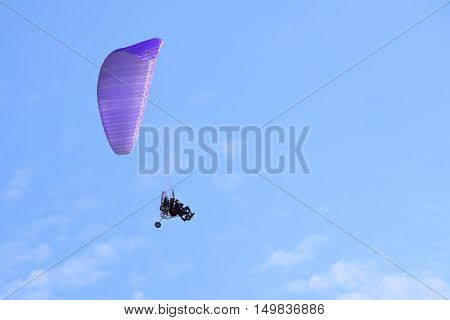 Powered purple paraglider flying through blue sky with two people