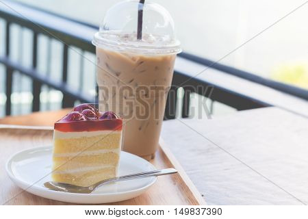 Sponge cake with cherry syrup. Peace of cherry cake serve with iced coffee.
