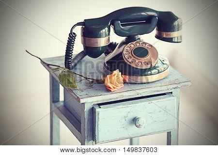 Vintage telephone on rustic blue nightstand