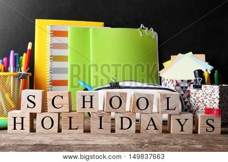 Word SCHOOL HOLIDAYS and stationery set on table