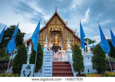 Chiang Mai Thailand - August 21: Woman pray at the Wat Phra Singh temple decorated with Queens Blue Flags on August 21 2016 in Chinag Mai Thailand.