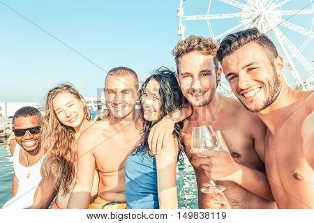 Group of multiracial friends having fun in boat summer party - Young people taking selfie photo with ferris wheel in background - Happiness and friendship concept - Warm vintage filter