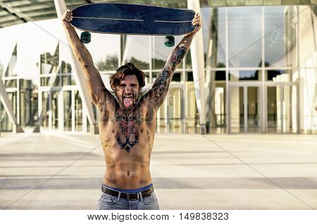 Bearded skater with tattoos holding longboard outside of conference center - Muscular man showing body in urban area - Rebel against system concept - Vintage editing - Warm filter