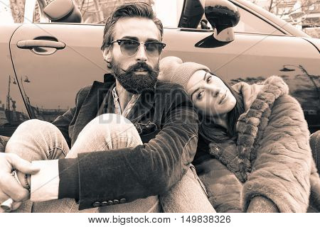 Fashion hipster couple sitting outside of cabriolet car - Lovers traveling around europe for road trip - Main focus on man - Black and white editing - Soft brown filter