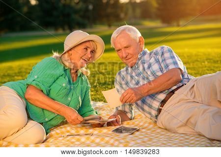 Couple lying on meadow. Senior man looking at photographs. That was long time ago. I remember our first date.