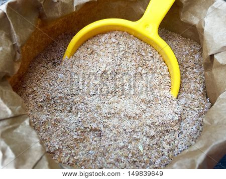 Wheat bran with a yellow shovel in a brown paper bag