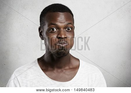Headshot Of Bug-eyed Young African Man Grimacing, Inflating His Cheeks, Holding His Breath, Trying H