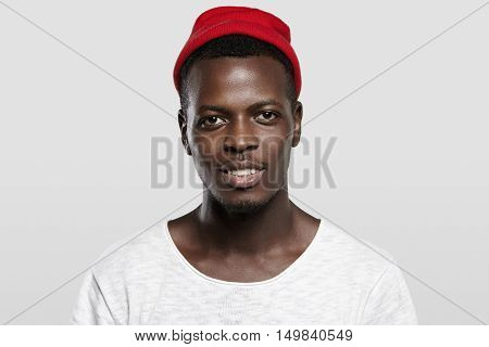 Open And Sociable. Handsome Happy Young Afro-american Hipster Wearing Red Trendy Hat, Smiling, Showi