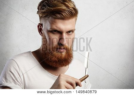 Attractive Redhead Hipster Barber With Stylish Haircut And Thick Beard Holding Cut-throat Razor, Loo