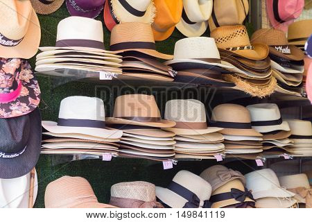 Market stall with craftsmanship hats in straw hats for sale.