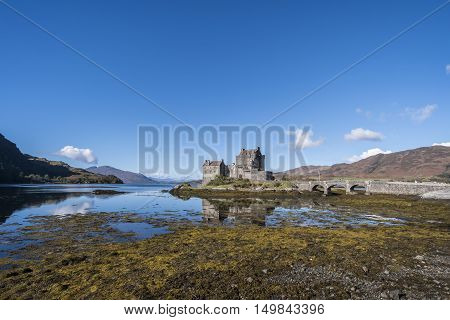 Beautiful Eilean Donan Castle 13th century fortification at Dornie Kyle of Lochalsh in the Scottish Highlands with clear blue sky and reflections