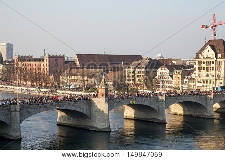 Basel, Switzerland - March 10, 2014: The bridge Mittlere Brucke filled with ddressed up people at the tradtional carnival parade