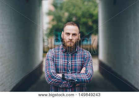 handsome man with a beard in a flannel shirt standing on the street