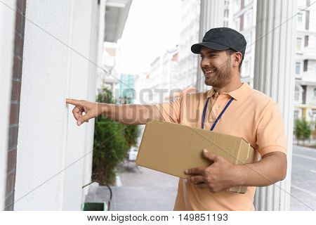 It is my job to be in time. Handsome young delivery man holding cardboard box while ringing doorbell of house
