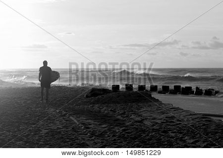 A black and white picture of a surfer walking down the beach at sunrise looking at the water