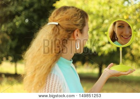 Young beautiful girl look into mirror in the park.Soft and blur conception.