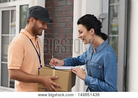 Always accuracy and punctuality in work. Side view of handsome delivery man holding cardboard box while beautiful young woman putting signature in clipboard