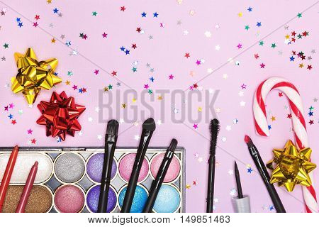 Christmas party makeup. Bright color glitter eyeshadow, mascara, eyeliner, red lipstick, lip liners, brushes and applicator with candy cane, gift wrap bows and confetti on pink background. Copy space