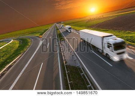Many white trucks in lieft driving towards the sun. Fast blurred motion image on the freeway at beautiful sunset. Freight scene on the motorway near Belgrade Serbia.
