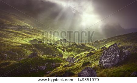 Unpredictable weather conditions in the beauty of wild mountainous terrain with sunbeams in the background. poster