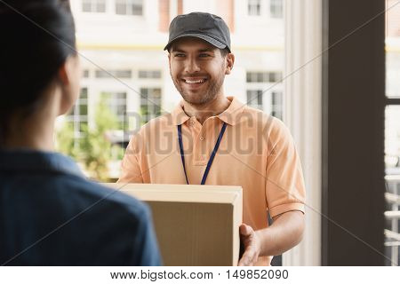 Handling your packages with care. Cheerful young delivery man giving cardboard box to woman while standing atentrance of her apartment