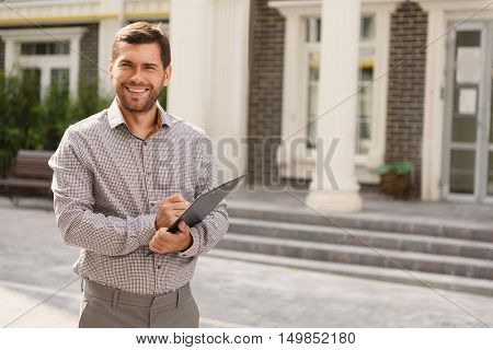 Real professional. Portrait of male realtor standing outside residential property, holding clipboard and smiling
