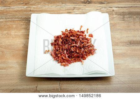 cooked bacon bits on a plate, wooden background