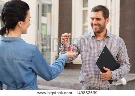 Best for you. Happy realtor man giving key to beautiful woman of new apartment and smiling