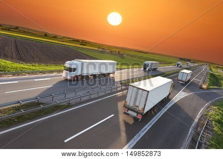 Many white trucks towards the sun. Fast blurred motion image on the freeway at beautiful sunset. Freight scene on the motorway near Belgrade Serbia.