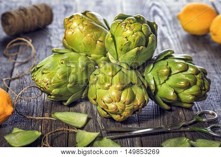 Ripe organic artichokes on the rustic wooden board with lemon selective focus.