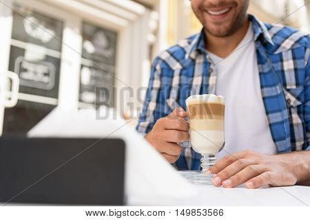 Sometimes I just need time to coffe break. Cropped shot of handsome young man enjoying cup of latte outside while spending time in cafe
