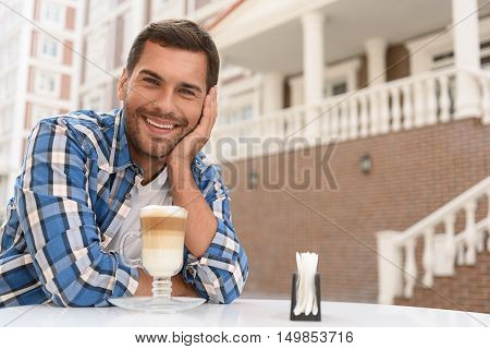 My favorite place for coffee. Cropped portrait of handsome man sitting in coffee shop outdoor, looking at camera and smiling