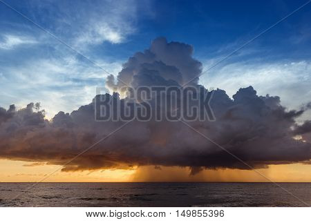 Calm sea on the sunset cloudy sky background