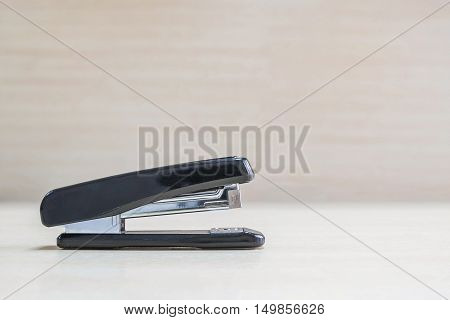 Closeup black stapler office equipment on blurred wood desk and wall in office room textured background under window light