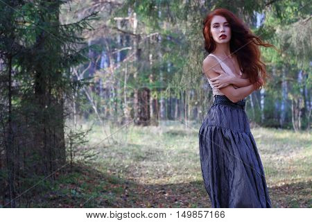 Sensual woman in skirt and belt poses on wind in sunny autumn forest