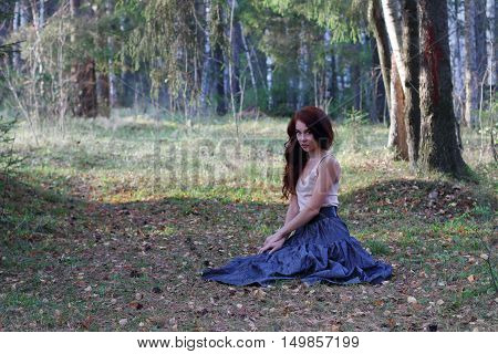 Sexy woman in skirt and belt sits on dry foliage in autumn forest full body