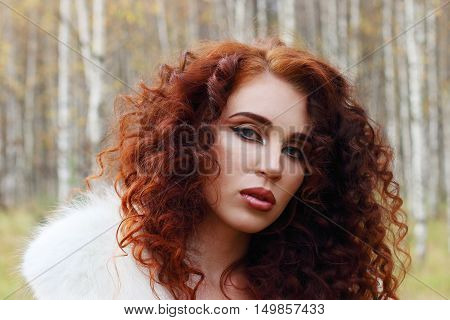Beautiful woman with white fur poses in autumn forest close up
