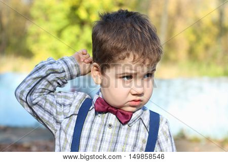 Plump little boy in shirt and bow tie thinks and scratches his head in sunny park