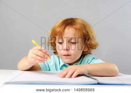 childhood and learning concept, cute little boy studying in kindergarten