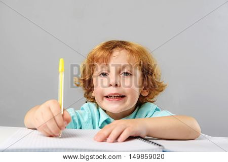 childhood and learning concept, concentrated preschooler drawing and looking into camera