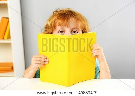 childhood and learning concept, little preschooler peeking out from behind the book