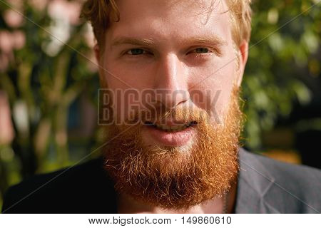 Happy hipster redhead man. Close up portrait of fun guy. Concept of beard cutting or hair style. Fire advertising. Interesting young man tell interview to the camera.