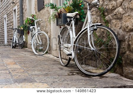 White bicycles as a decoration in an old stone fortress