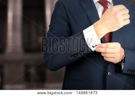 business and office concept - elegant young fashion buisness man in a blue/navy suit touching at his cufflinks