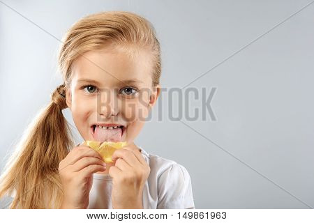 prophylaxis and health care concept, close up of funny child licking sour lemon