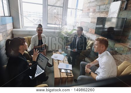 Four young business colleagues meeting in modern office. Business people discussing working during meeting.