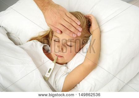 sickness and child care concept, kid being checked for cold