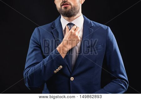 Confident young businessman is adjusting his tie. He is standing and posing. Isolated on black background